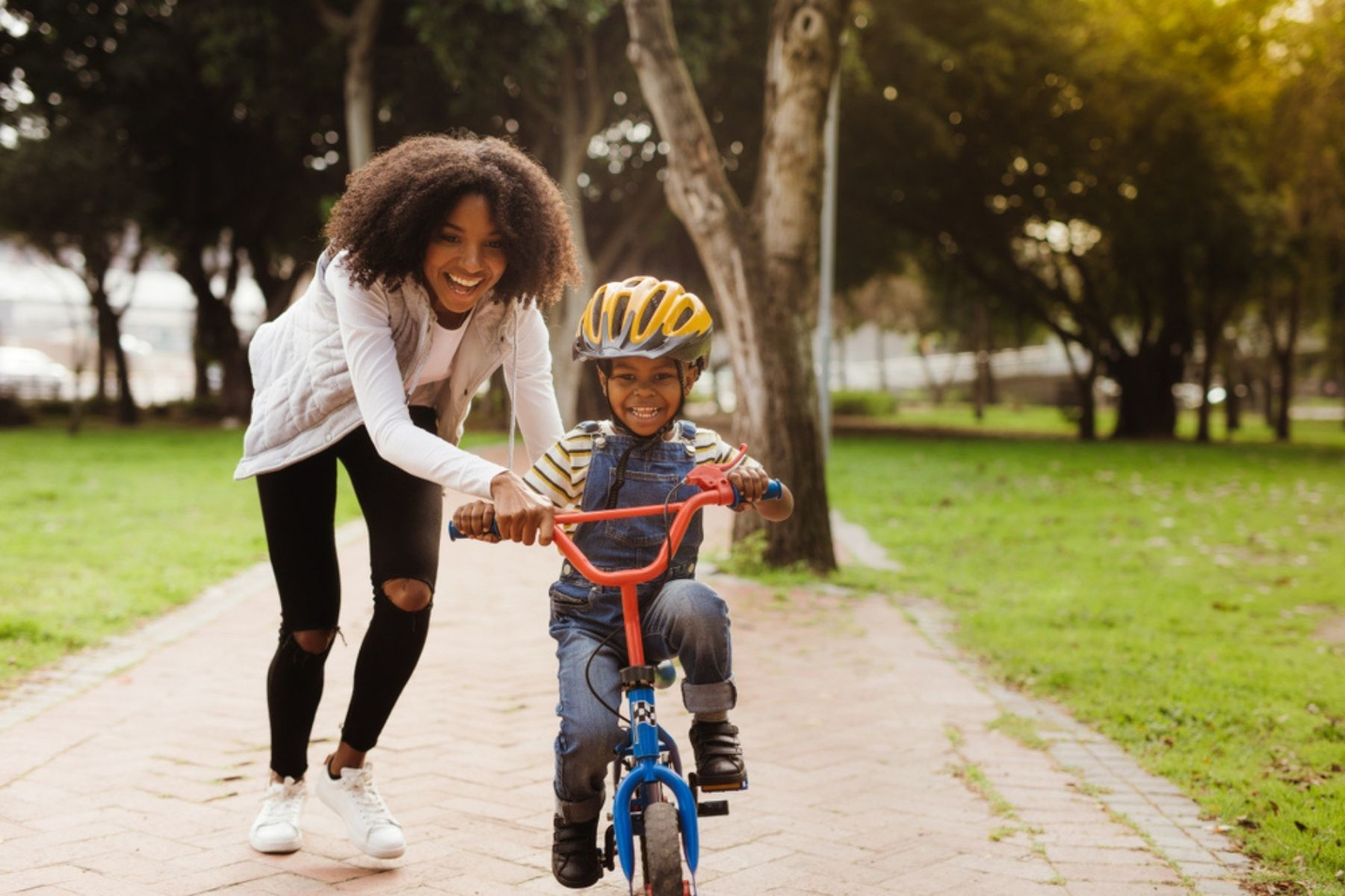 Image is of woman and child with a bike