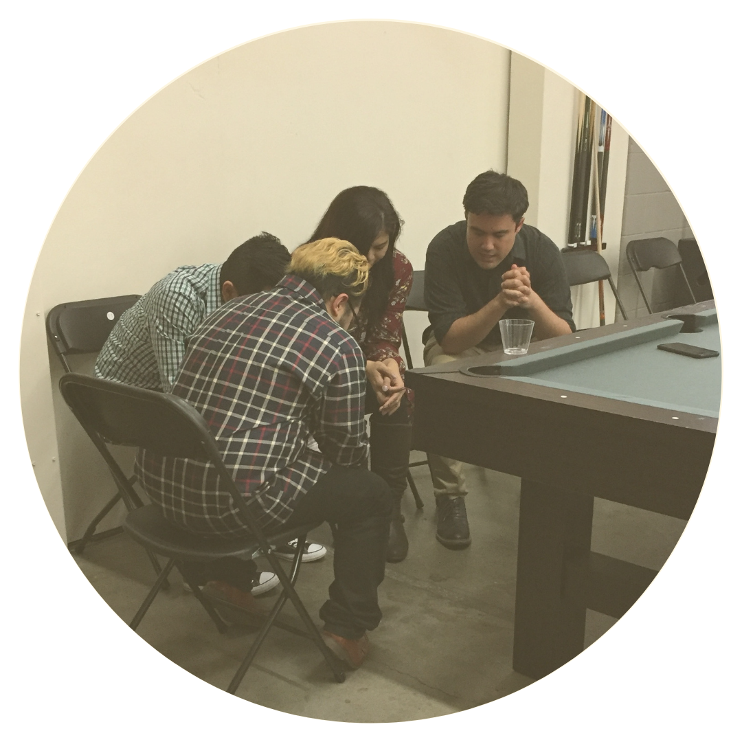 four people praying in a group