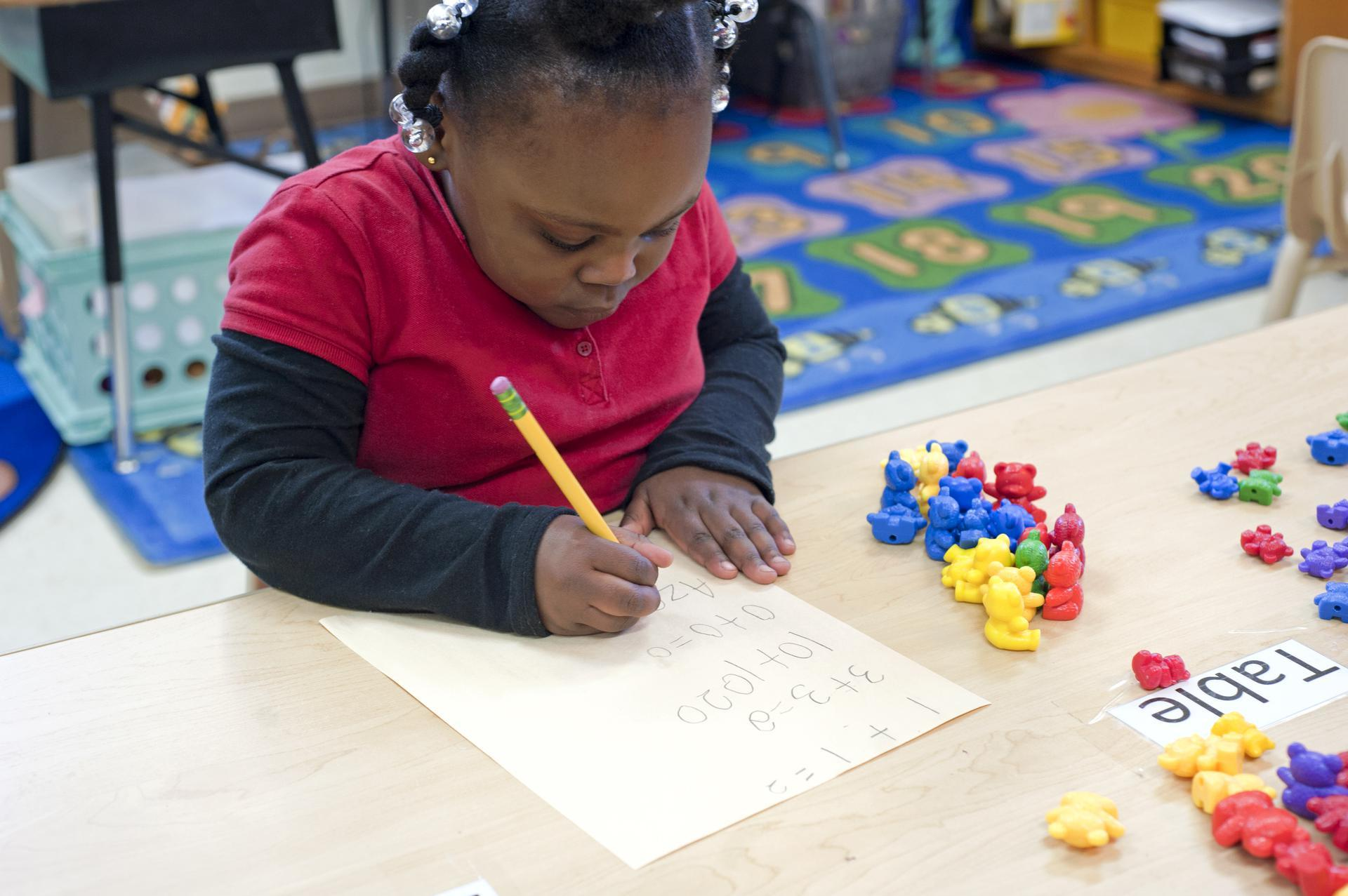 A 4-year-old kindergartner seated in a classroom uses a pencil to write on a sheet of paper