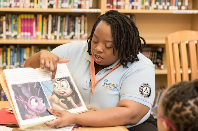 AmeriCorps member reading to a child