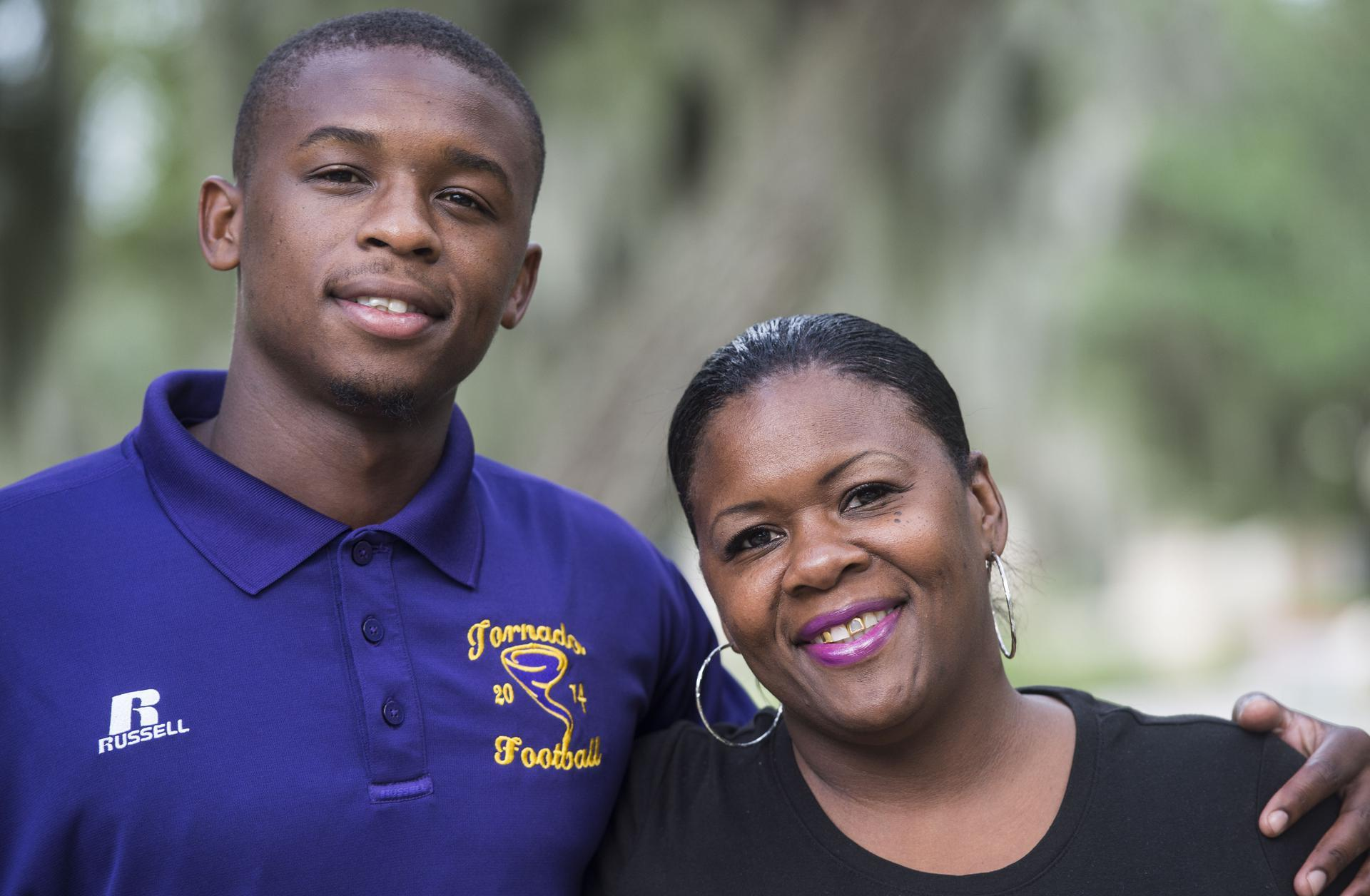 A young man and his mother, both smiling.