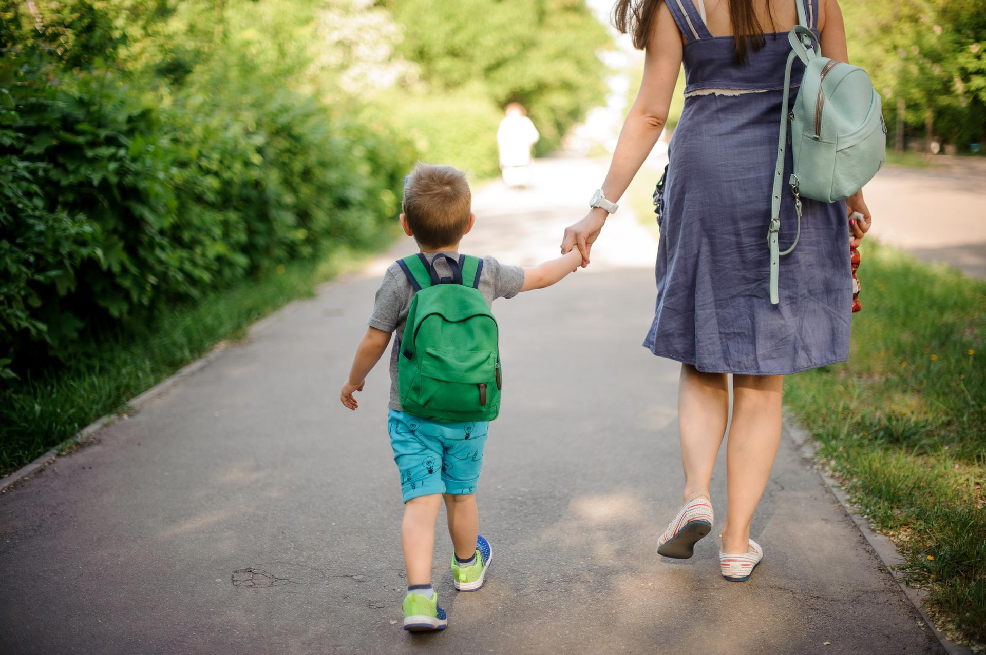 View from behind of a woman holding the hand of a boy wearing a green backpack as they walk down a sidewalk