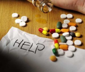 """assorted pills on a table with a white piece of paper that says """"HELP"""""""